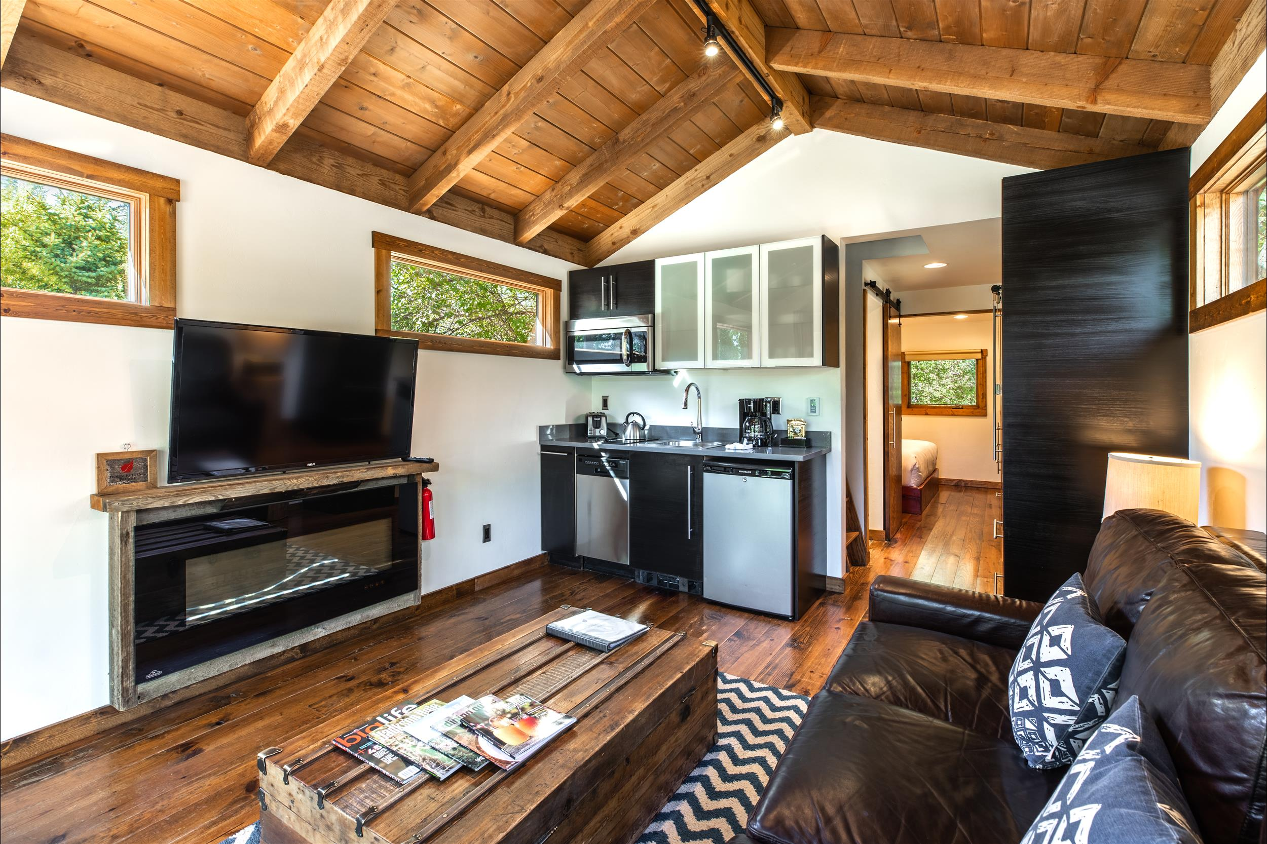 modern cabin living room with flatscreen tv and kitchenette jackson hole wy